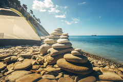 Stone Zen Pyramids At Beach With Tourist Tent On A Background. Concept Of Harmony And Balance Royalty Free Stock Photos