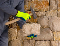 Stonecutter mason with hammer and stone working masonry. Stonecutter mason with hammer and stone building a masonry stone wall Royalty Free Stock Photos