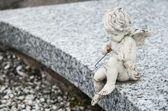 Stoned angel sitting on tomb with violin in a cemeter. Closeup of stoned angel sitting on tomb with violin in a cemetery Royalty Free Stock Photo