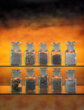 Stoned jars. Ten chemical jars filled by various types of minerals, fire like background Stock Photography