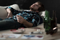 Stoned man. Young handsome stoned men lying on a couch stock photo