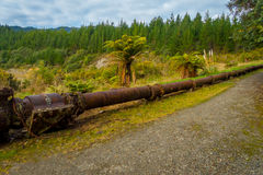 Stoned road with a rusted pipeline in one side of the road in south island, in New Zealand.  Royalty Free Stock Image