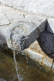Stoned Water Source. Drinking water falling from the stoned water source to the trough. Photo taken in Bansko, Bulgaria Royalty Free Stock Photo