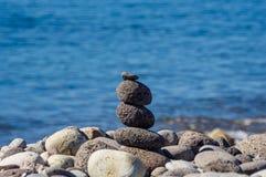Stonefigure e peebles na frente do azul, oceano borrado foto de stock royalty free