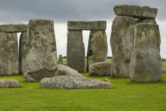 Stonehenge. The ancient Stonehenge Monument highlighted by grey skies and a field of green Stock Image