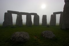 Stonehenge at dawn on a foggy day. A view of Stonehenge on a foggy morning, with the sun rising over the stones Royalty Free Stock Images