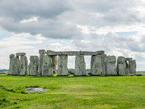 Stonehenge in England. Stonehenge an ancient prehistoric stone monument near Salisbury, Wiltshire, England, with unrecognized tourist nearby. Stonehenge is the royalty free stock photo