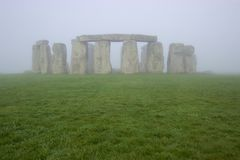 Stonehenge on a foggy morning. The ancient standing stones of Stonehenge shown across a grassy field Stock Image