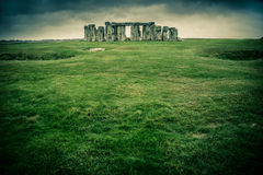 Stonehenge. Grass field leading to Stonehenge on a cloudy gray day Royalty Free Stock Images