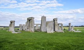 Stonehenge prehistoric monument, green grass, blue sky and clouds - Wiltshire, Salisbury, England Royalty Free Stock Photos