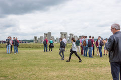Stonehenge with tourists. Many tourists visiting Stonehenge listening and learning the history Royalty Free Stock Photos