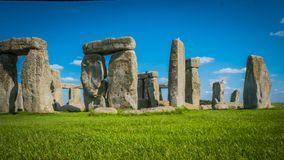 Stonehenge UNESCO dziedzictwo w UK bocznym widoku za zieleni polem obraz royalty free