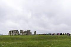 STONEHENGE, WILTSHIRE, HET UK - 17 AUGUSTUS: Toeristen die voor een rij vormen Royalty-vrije Stock Foto