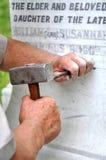 Stonemason Engraving Marble Gravestone. Stonemason using traditional skills to engrave a white marble gravestone Stock Photography