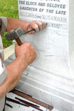 Stonemason Engraving Marble Gravestone. Stonemason using traditional skills to engrave a white marble gravestone Royalty Free Stock Photo