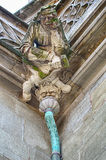 Stonemason Gargoyle Over Drain. A detailed figure of a stonemason carved in stone sits over a demon on top of one of the drains on the Bern Minster Cathedral in Royalty Free Stock Images