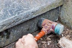Stonemason knocks riser. Craftsmen knocks with a rubber hammer on stone Stock Photo