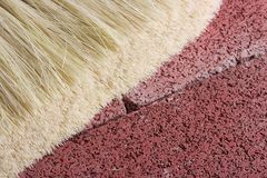 Stonemason's brush. On a red brick background Stock Photos