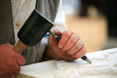 Stonemason at work. A stonemason working with hammer and chisel Stock Photos