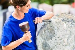 Stonemason working on boulder with sledgehammer and iron. Female stonemason working on boulder with sledgehammer and iron Stock Images