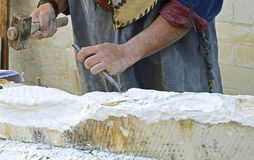 Stonemason working with hammer and chisel. Stonemason working on a cube of sandstone with hammer and chisel Royalty Free Stock Images