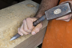Stonemason. A stonemason working a large stone block of sandstone with a hammer and chisel Royalty Free Stock Photography