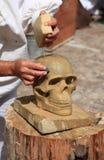 Stonemason working on a sandstone skull. A stonemason working on a sandstone skull Royalty Free Stock Photo