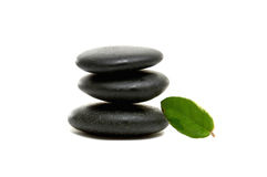 Stones. Balanced black zen pebbles and a young green leaf Royalty Free Stock Photography