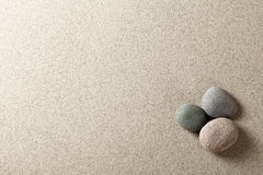 Stones. Three colorful round stones on sand background Royalty Free Stock Images