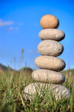 Stones. Round stones lays on a grass. Blue sky on a background Stock Photography
