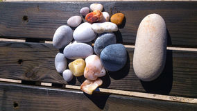 Stones of Aegean sea on the wooden bench. Stones from the beach of Aegean sea 10 km away from Kusadasi resort,Aydin province,west Turkey.Smoothy stones have Stock Photo