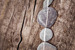 Stones aligned on wood Stock Photo