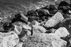 Stones along the rugged coast pacific ocean. Black and white photo Stock Image