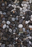 Stones background. A close up view of smooth polished multicolored stones washed ashore on the beach Stock Photos