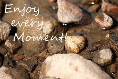 Stones Background With Copy Space. Stones In Water As Background Or Backgrop Or Card. English Life Quote Enjoy Every Moment. Close Up Or Macro View. Sunny Summer royalty free stock images