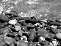 Stones on background of sea water with reflections. Black and white royalty free stock photography