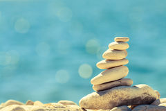 Stones balance at the beach, stack over blue sea Stock Photos