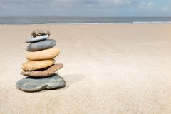 Stones balance and harmony pebbles stack on the sand beach during daytime on a sunny day. Concept of Stones balance and harmony pebbles stack on the sand beach Royalty Free Stock Photos