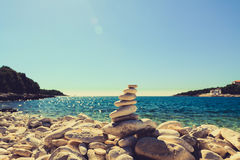 Stones balance, pebbles stack over blue sea in Croatia. Stones balance at the vintage beach, inspirational summer landscape. Stability hierarchy stack over blue Royalty Free Stock Images