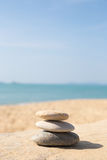 Stones balance, pebbles stack on sunny sea beach. Stones balance, pebbles stack on the sand beach with shadow on right side , beautiful sea view during daytime Stock Photography