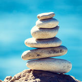 Stones balance, vintage pebbles stack background. Stones balance, vintage retro instagram like hierarchy stack over blue sea background. Spa or well-being Royalty Free Stock Images