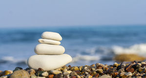 Stones balance, vintage retro instagram like hierarchy stack ove. R blue sea background. Spa or well-being, freedom and stability concept on rocks stock image