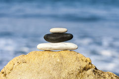 Stones balance, vintage retro instagram like hierarchy stack ove. R blue sea background. Spa or well-being, freedom and stability concept on rocks royalty free stock photo