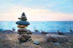 Stones laid out in the form of a pyramid on the seashore. Stones balance and wellness retro spa concept, inspiration, zen-like and well being tranquil Royalty Free Stock Photos