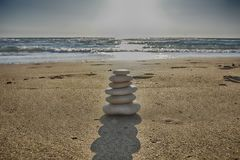 Stones balance and wellness retro spa concept, inspiration, zen-like and well being tranquil composition. Close-up of white pebbles stack over blue sea royalty free stock image