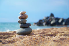Stones laid out in the form of a pyramid on the seashore. Stones balance and wellness retro spa concept, inspiration, zen-like and well being tranquil Royalty Free Stock Image