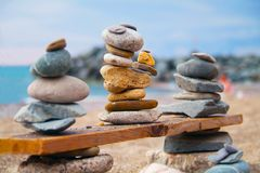 Three pyramids of stones laid out on wooden board at the seashor. Stones balance and wellness  spa concept, inspiration, zen-like and well being tranquil Royalty Free Stock Photos