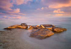 Stones on a beach. Stones on a sandy beach at sunrise stock images
