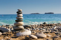 Stones on the beach. Pyramid of stones on the beach near the sea stock images