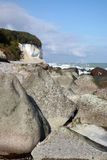 Stones on the beach of Ruegen in Germany with the chalk cliffs in the background Stock Photography